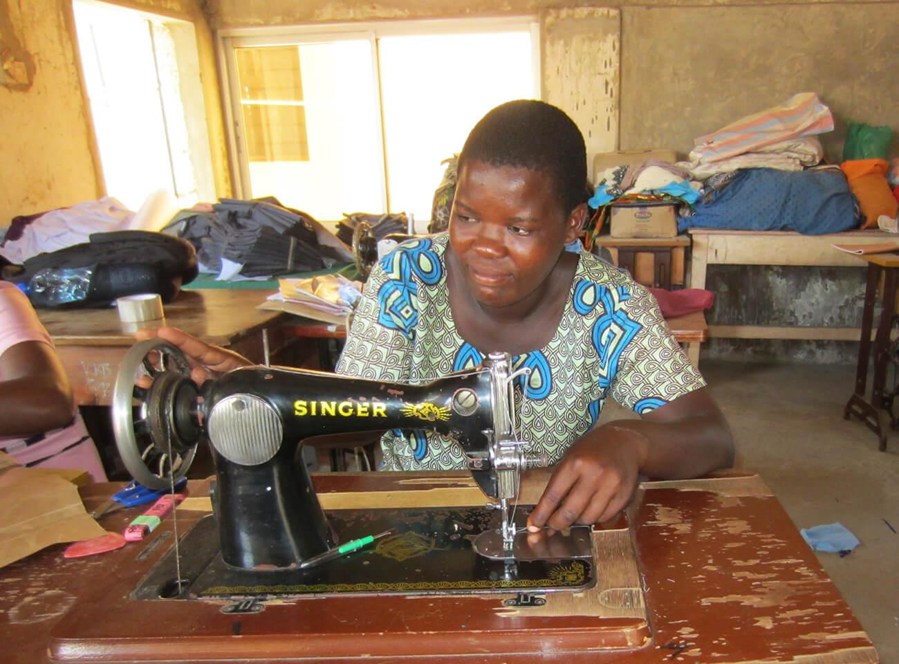 Dama Kahindi on a sewing machine